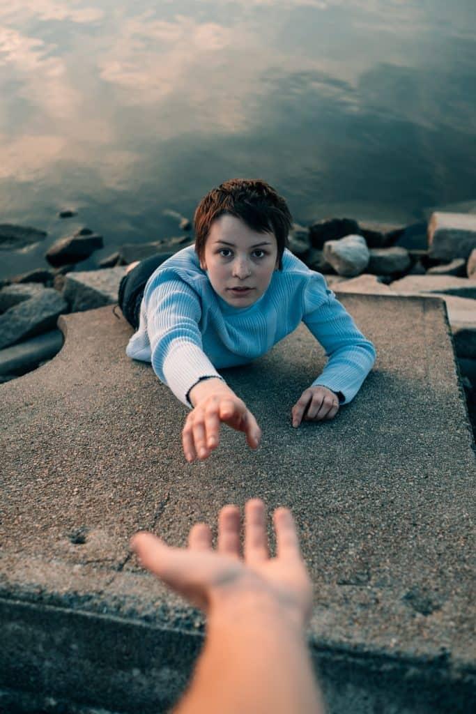 En kvinna som sträcker sig efter en utsträckt hand. Hon ligger på en klippa och har havet i bakgrunden.